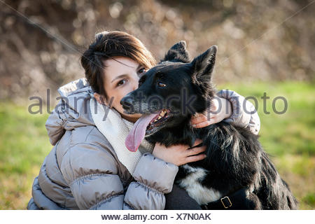 Portrait of mid adult woman kissing her dog in field - Stock Photo