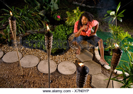 Young Jamaican man with dreadlocks sitting in tropical garden - Stock Photo