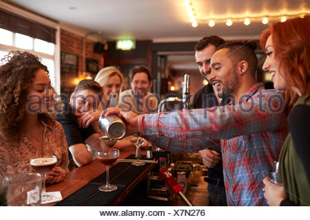 Man Learning How To Mix Cocktail At Lesson In Bar - Stock Photo