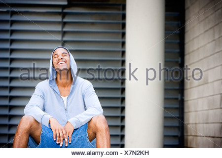 Portrait of a young smiling African American man in a grey hooded top sitting on a basketball. - Stock Photo