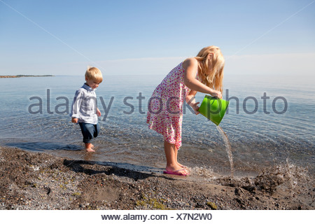 Young Girl And Her Brother Playing On The Beach By Lake Ontario;Ontario Canada - Stock Photo