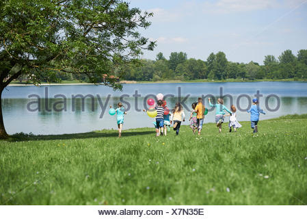 Rear view of children running in park with balloons, Lake Karlsfeld, Munich, Bavaria, Germany - Stock Photo