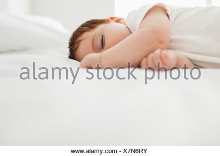 Baby girl sleeping on bed - Stock Photo