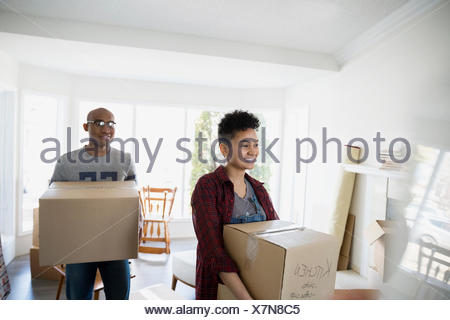 Couple carrying moving boxes in living room - Stock Photo