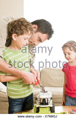 father fixing toy with son - Stock Photo