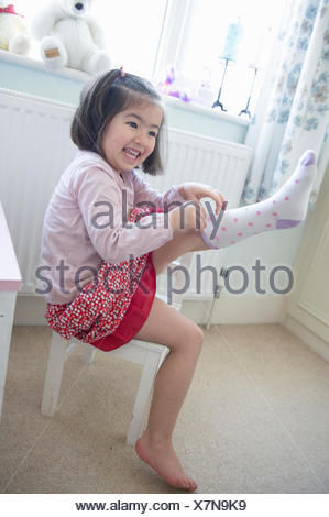 Young girl sitting on chair, pulling sock on - Stock Photo