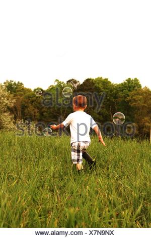 Boy Playing With Soap Bubbles - Stock Photo