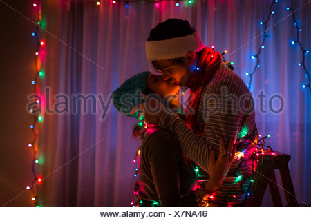 Young couple kissing whilst wrapped in fairy lights at christmas - Stock Photo