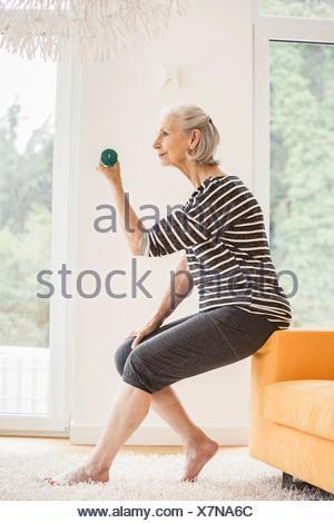 Senior woman sitting on sofa exercising with dumbbell - Stock Photo