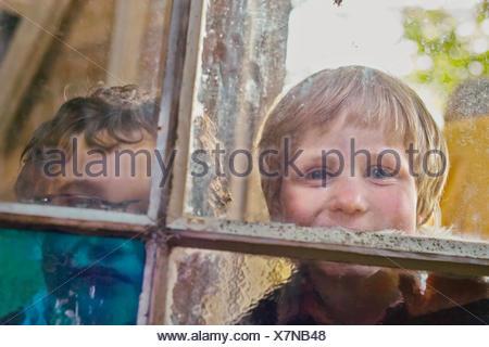 Portrait of two boys looking through hut window - Stock Photo