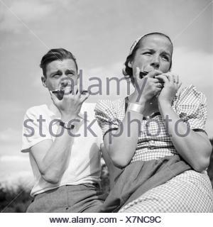 Ein Mann und eine Frau spielen Mundharmonika, Deutschland 1930er Jahre. A man nand a woman playing harmonica, Germany 1930s. - Stock Photo