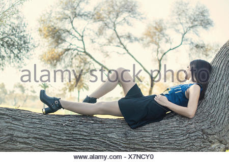 Young woman lying on tree - Stock Photo