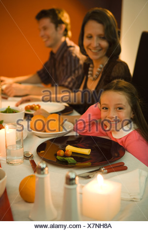 Girl sitting at dinner table, smiling at camera, adults in background - Stock Photo