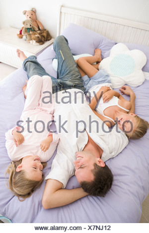 Man lying in bed with two young girls smiling - Stock Photo