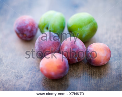 Green and purple plums on wooden table - Stock Photo