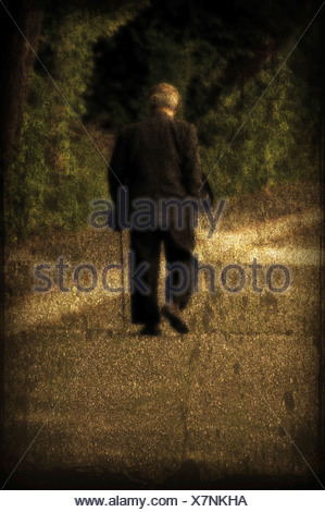 An elderly man with a cane walking along seawall. - Stock Photo