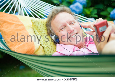 Close-up of a mature man listening to music and lying in a hammock - Stock Photo
