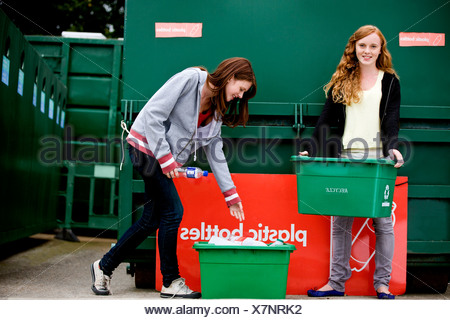 Two teenage girls recycling plastic bottles - Stock Photo