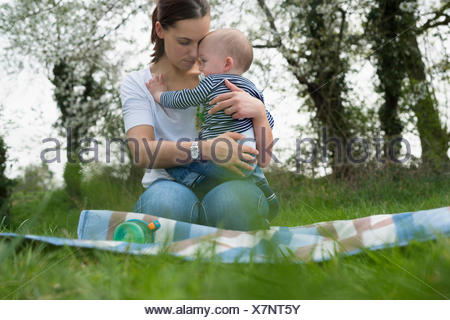 Young mother hugging baby son on picnic blanket in field - Stock Photo