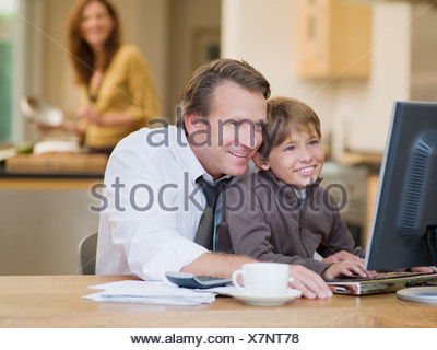 Businessman and son using computer - Stock Photo