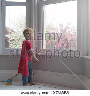 Boy dressed like superhero, looking through window - Stock Photo