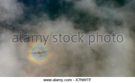 Aerial view, airplane with cloud shadows and diffuse circular rainbow - Stock Photo