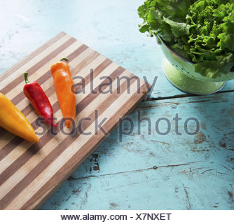 A tabletop with a wooden chopping board and three sweet peppers and a bowl of salad leaves - Stock Photo