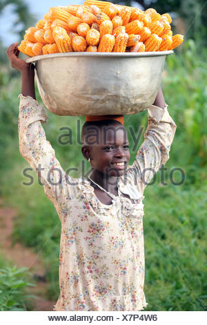Girl carrying platter with corn on head. togo. - Stock Photo