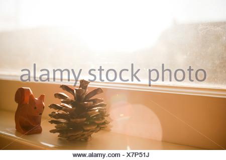 Pine cone and squirrel ornament on windowsill - Stock Photo