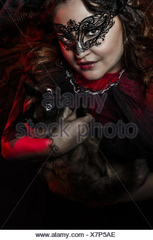 woman caressing a Siamese cat - Stock Photo