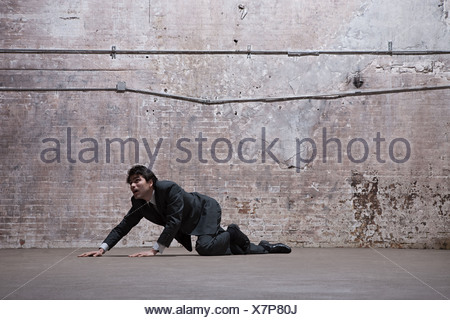 Man lying on warehouse floor - Stock Photo