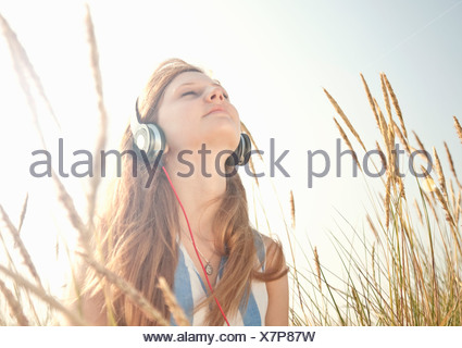 Teenage girl listening to music outdoors - Stock Photo
