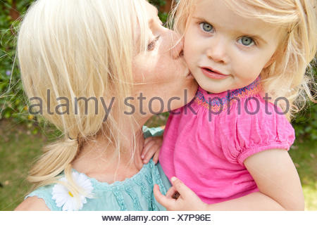 Close up of young adult mother kissing toddler daughter in garden - Stock Photo