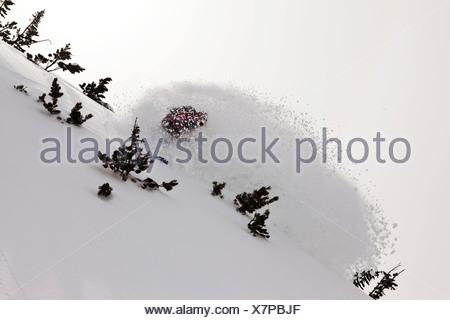A athletic snowboarder rips fresh deep powder turns in the backcountry on a stormy day in  Montana. - Stock Photo