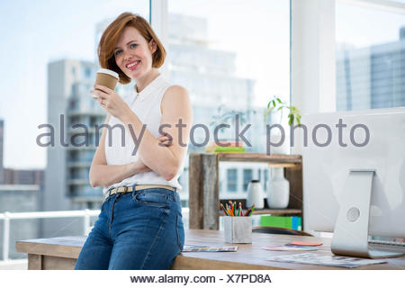 smiling hipster business woman drinking coffee in her office - Stock Photo
