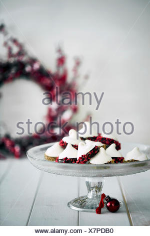 Christmas decorations and meringues on cake stand - Stock Photo