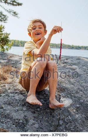 Sweden, Uppland, Runmaro, Barrskar, Portrait of boy (6-7) holding grass with berries - Stock Photo