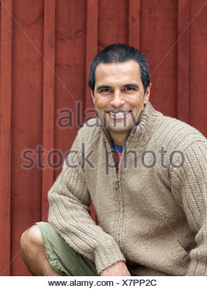 Man crouching in front of red wall smiling. - Stock Photo