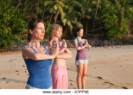 Women practicing yoga on a beach - Stock Photo