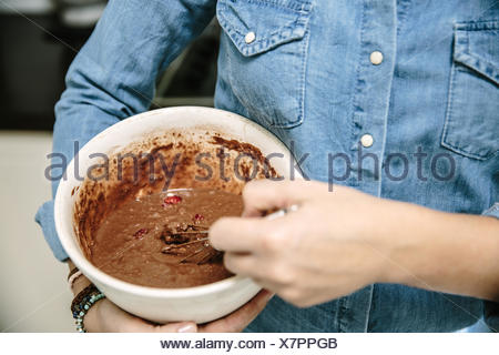 Woman holding bowl and mixing chocolate cake batter - Stock Photo