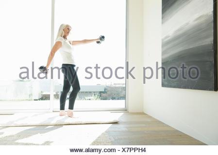 Senior woman exercising with dumbbells - Stock Photo
