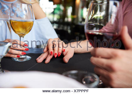 Cropped view of woman's hand on boyfriend's hand at restaurant table - Stock Photo