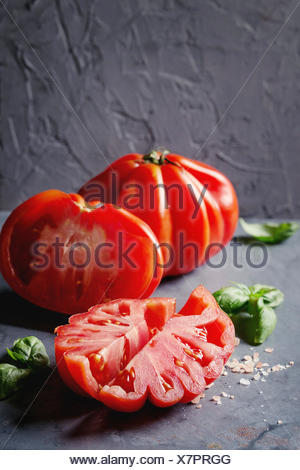 Whole and sliced organic tomatoes Coeur De Boeuf. Beefsteak tomato with pink salt and basil on blue gray metal texture background. Close up with space - Stock Photo