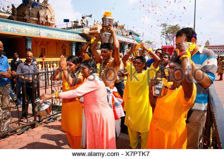 Pilgrims making a milk sacrifice, Hindu festival Thaipusam, Batu Caves limestone caves and temples, Kuala Lumpur, Malaysia - Stock Photo