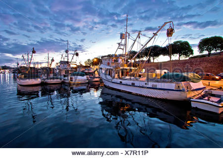 Fishing boats on colorful sunset - Stock Photo