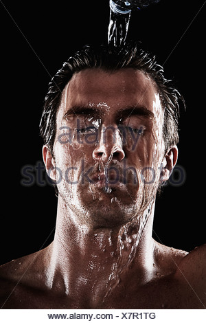 Man pouring water over head - Stock Photo