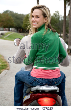 A young woman sitting on the back of her boyfriends scooter - Stock Photo