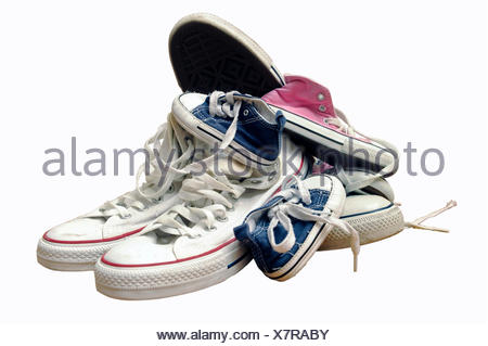 Sneakers or trainers of a whole family gathered in one heap - Stock Photo