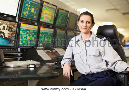 Woman working in security control room - Stock Photo