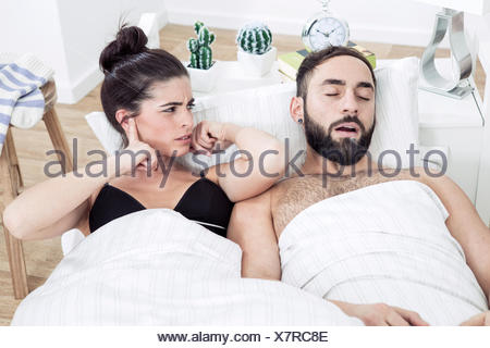 Couple lying in bed with man snoring - Stock Photo